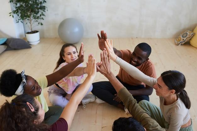 Группа людей, сидящих на полу и отдающих пять во время урока терапии