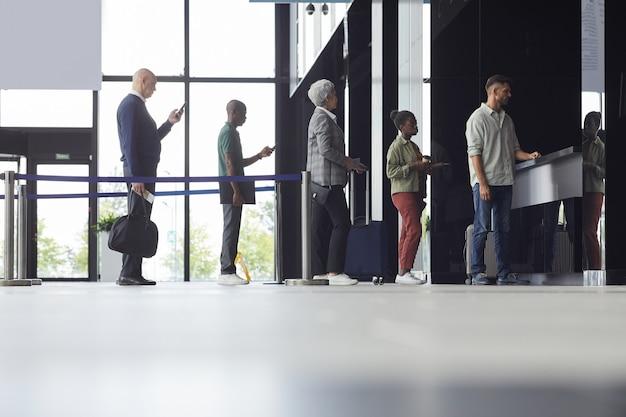Группа людей, стоящих в ряду и покупающих билеты на самолет в аэропорту