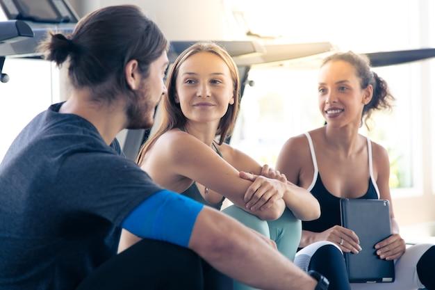 Группа людей разговаривает и смеется, счастливы вместе после тренировки в тренажерном зале. концепции здорового образа жизни и спорта.