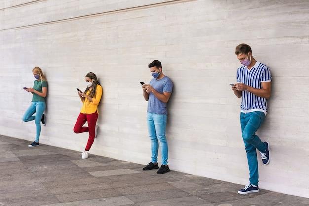 사회적 거리를 유지하면서 줄을 서서 기다리는 휴대 전화를 사용하는 사람들의 그룹