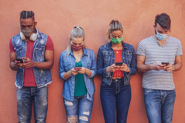 フェイスマスクで保護されたスマートフォンを19回covidで使用している人々のグループ-友達が壁に立って携帯電話を持ちながらオンラインニュースをチェック
