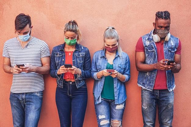 スマートフォンをcovidで使用している人々のグループ-フェイスマスクで19回保護