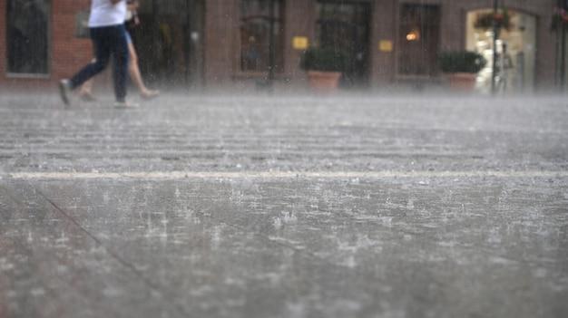 Группа людей, идущих по улице в дождливый день в размытом изображении