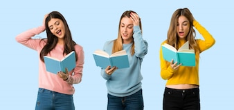 Group of people with colorful clothes surprised while enjoying reading a book on colorful