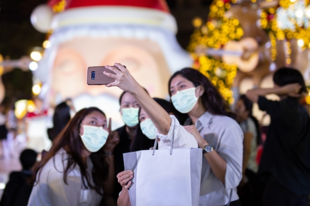 크리스마스 트리 앞에서 보호 마스크 셀카를 가진 사람들의 그룹