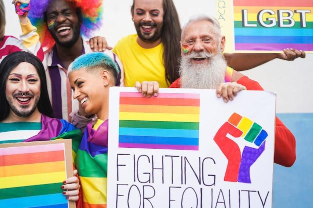 ゲイプライドイベント中に虹色の旗とバナーを持つ人々のグループ