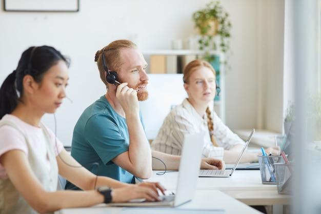 Группа людей, работающих в колл-центре, они в наушниках сидят за столом и консультируют клиентов