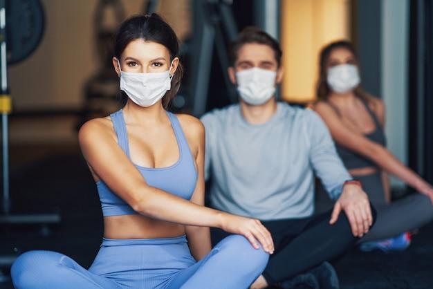 Группа людей, тренирующихся в тренажерном зале, в масках из-за covid-19