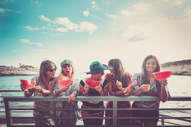 若い陽気な幸せな女性の人々のグループは、夏の新鮮なスイカを食べる青い空と海と一緒に屋外で友情を祝い、楽しんでいます