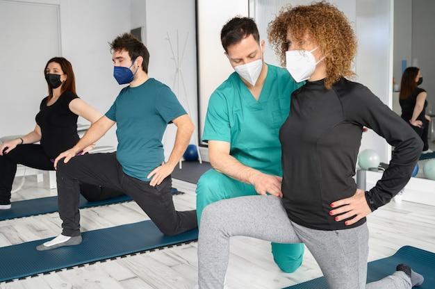 재활 클리닉에서 물리 치료사의 도움을받는 요가 매트에있는 사람들의 그룹입니다.