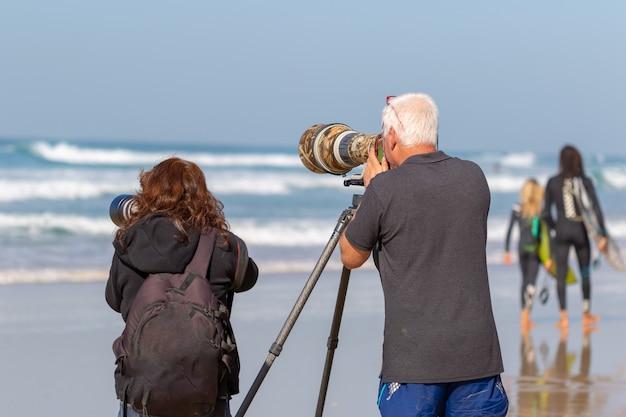 Группа фотографов снимает на море фотографии с очень большими объективами.