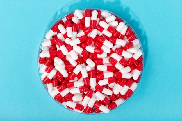 青の背景に丸い容器の錠剤カプセルのグループ。白と赤の錠剤。医学、医療、薬局のコンセプト