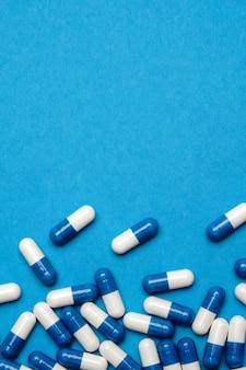 Группа таблеток или капсул на синем фоне.