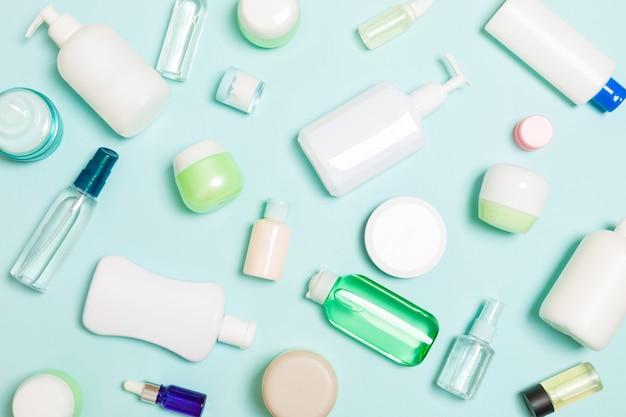 플라스틱 바디 케어 병의 그룹 파란색 표면에 화장품과 평면 누워 구성