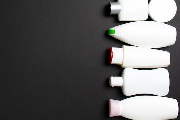 プラスチック製のボディケアボトルのグループあなたがデザインするための色付きの背景の空きスペースに化粧品を含むフラットレイ組成物。白い化粧品コンテナのセット、コピースペースと上面図。