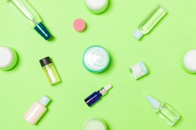 플라스틱 바디케어 병 그룹은 당신이 디자인할 수 있는 녹색 배경 빈 공간에 화장품이 있는 평평한 구성입니다. 흰색 화장품 용기 세트, 복사 공간이 있는 위쪽 보기.