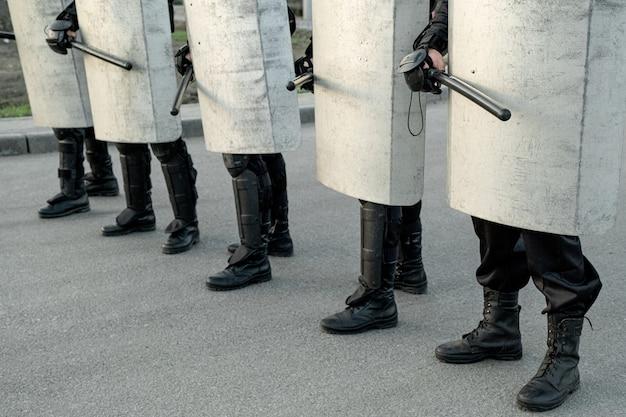 Группа полицейских движется с дубинками по улице, проводя скоординированные действия против протестующих