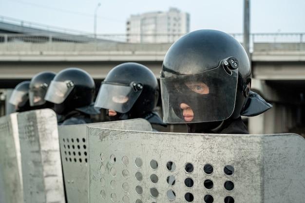 활동가를 야외에서 막으면서 보호를 위해 진압 방패를 사용하는 제복을 입은 경찰 그룹