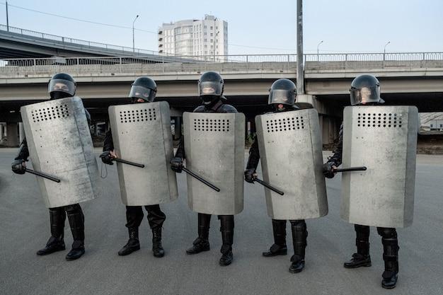 거리에 줄지어 서 있는 측면 손잡이 지휘봉과 금속 방패를 들고 헬멧을 쓴 경찰 경비