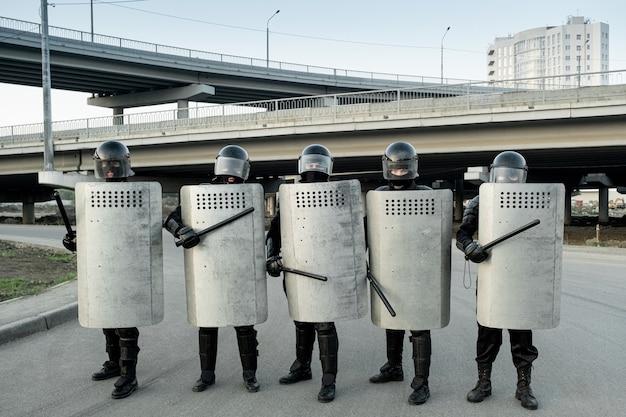 측면 손잡이가 있는 방패로 보호되는 제복을 입은 경찰 경비원과 도시 다리에 대한 방패