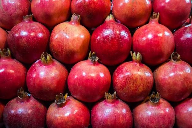 Группа гранатов. гранатовый крупный план, фон. спелые фрукты аккуратно разложены на прилавке в магазине