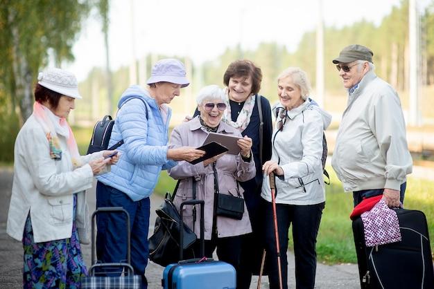 Группа позитивных пожилых людей старшего возраста, глядя на цифровую карту в путешествии.