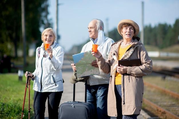 旅行の旅で地図を見ているポジティブな高齢者のグループ。