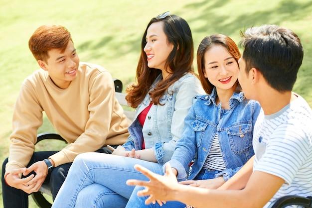 긍정적인 대학생 그룹은 야외 캠퍼스에 앉아 새 수업과 방학에 대해 토론합니다.