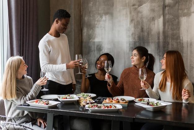 Группа позитивных молодых людей тостов за ужином