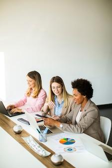 新しいプロジェクトに取り組んでいるかなり若い多民族のビジネス女性のグループ