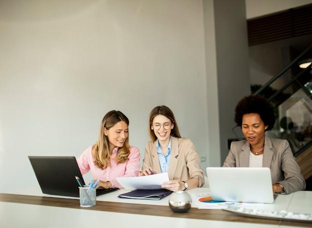 Группа довольно молодых многонациональных деловых женщин, работающих над новым проектом