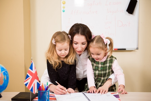 교실에서 책상에서 일하는 초등 학생 및 교사의 그룹입니다.