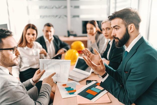 Группа профессиональных архитекторов, сидящих за столом и работающих над проектом. избавьтесь от отвлекающих факторов, соберите сосредоточенность.