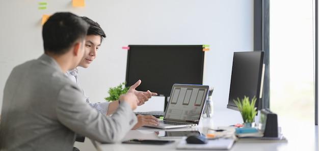 近代的なオフィスで一緒にスマートフォンテンプレートに取り組んでいるプロのuxグラフィックデザイナーのグループ