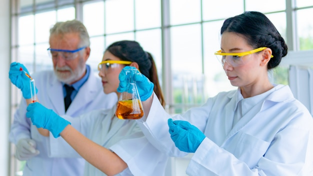 白いガウンを着た教授研究者科学者のグループは、机の上に科学機器を備えた試験用化学液体を準備します。顔集中。