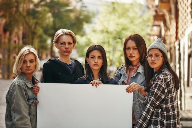 빈 간판을 들고 카메라를 보는 동안 항의하는 젊은 여성 활동가 그룹
