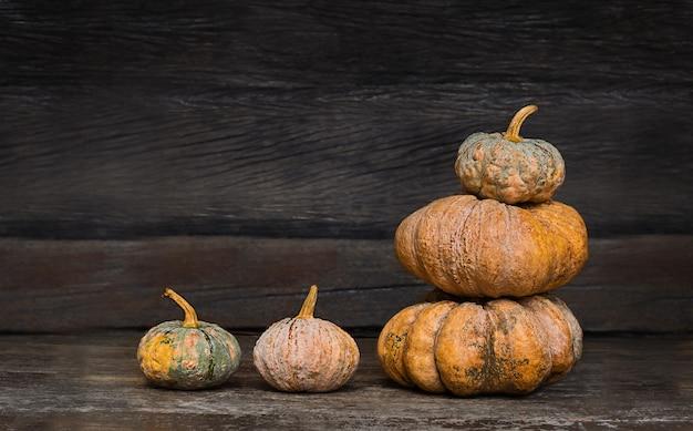 暗い古い木製の背景にカボチャのグループ。さまざまな種類のカボチャを収穫する