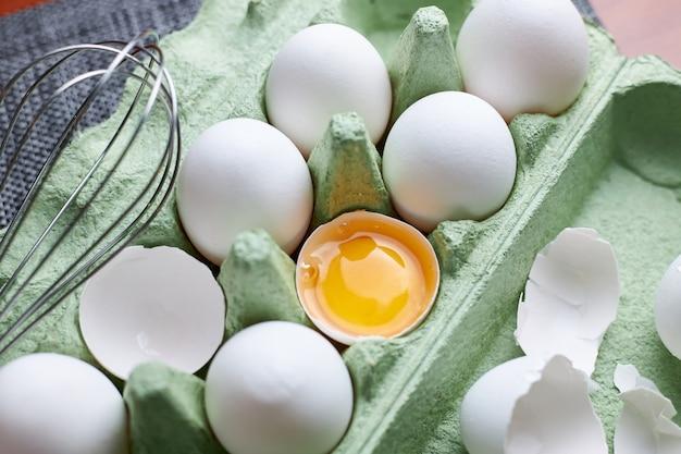木製のテーブルの上の緑の紙トレイ、新鮮な半分ひびの入った卵とステンレス鋼の卵泡立て器で生の白い鶏の卵のグループ。健康的なライフスタイルの概念。