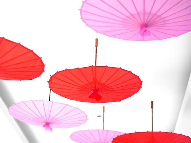バレンタインと中国の旧正月の祭りの装飾のために天井にぶら下がっている赤とピンクの紙傘のグループ。