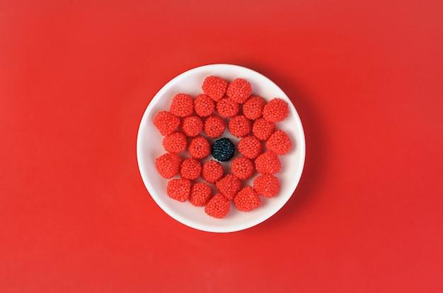 흰색 접시에 빨간색 씹는 사탕과 하나의 검은 사탕의 그룹