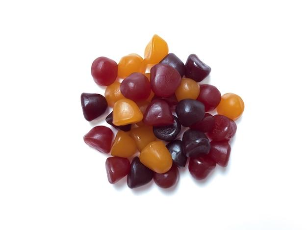 白の背景に分離された赤、オレンジ、紫のマルチビタミングミのグループ。健康的なライフスタイルのコンセプト。