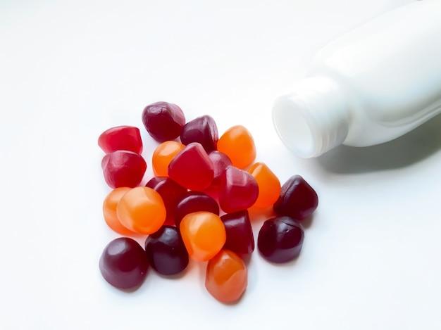 白の背景に分離されたボトルと赤、オレンジ、紫のマルチビタミングミのグループ。健康的なライフスタイルのコンセプト。