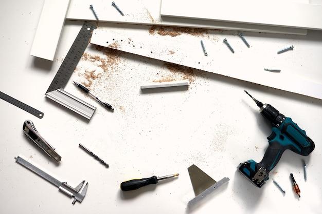 Группа инструментов для ремонта на деревянной белой поверхности