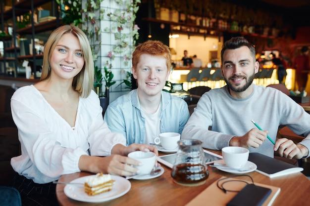 Группа спокойных счастливых студентов колледжа сидит за столиком в кафе после занятий, пьет чай и делает домашнее задание