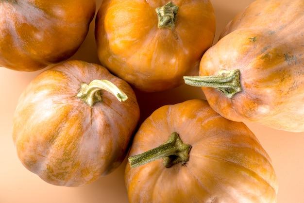 熟した秋のカボチャのグループ、ベージュのカラフルな背景の構成秋の収穫セール、感謝祭の休日の背景
