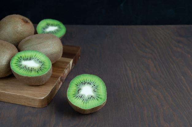 黒の背景に暗い木製のテーブルのまな板に熟した緑のキウイフルーツのグループ