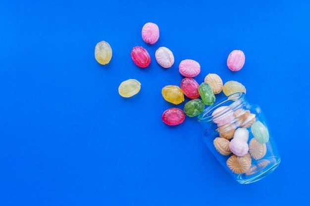 유리 항아리와 파란색 배경에 흩어져있는 다채로운 사탕의 그룹입니다. 제과 및 과자 가게 개념입니다. 재고 사진.