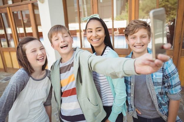 携帯電話でselfieを取る学校の友人のグループ