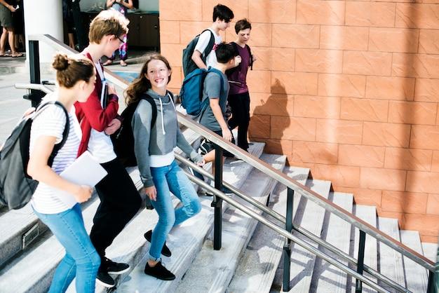 Группа школьных друзей спускается по лестнице