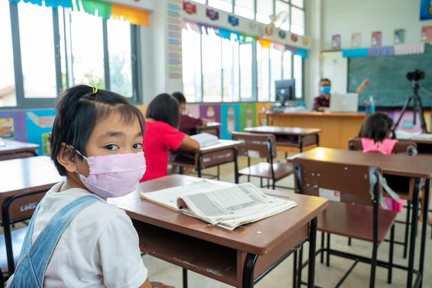ウイルスから彼女を保護するために医療用マスクまたはサージカルマスクを身に着けている学校の子供たちのグループは、教室、保護covid-19およびコロナウイルス感染で勉強しています。